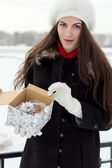 Cheerful Caucasian Young Woman in Snowy Weather opens a box with — Stock Photo