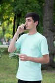 Attractive young guy outdoors calls by telephone — Stock Photo