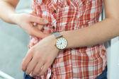 Girl clasps Wristwatch — Stock Photo