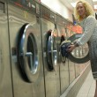 Laundromat girl inserting clothes — Stock Photo