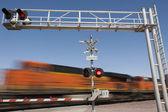 Train speeding by railroad crossing — Stock Photo