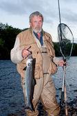 Fisherman with salmon — Stock Photo