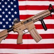 Assault rifle on american flag — Stock Photo