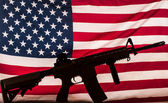 Gun silhouette on american flag — Stock Photo