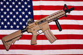 Assault rifle on american flag — Stock Photo