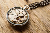 Pocket watch mechanism on wood background — Stock Photo