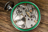 Pocket watch mechanism wood background — Stock Photo