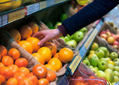 Choosing an orange in grocery store — Stok fotoğraf