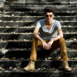 Attractive young handsome man, model of fashion in stairs — Stock Photo