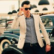 Attractive man wearing jacket and shirt with old cars - Stockfoto