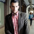 Portrait of a young handsome man, model of fashion, wearing jacket and shirt in urban background — Stock Photo #19284851