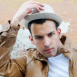 Attractiv young man with a hat in urban background - Stock Photo