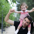 Little girl walking on the shoulders of her father — Stock Photo