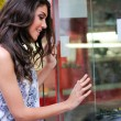 Portrait of an attractive young woman looking at the shop window — Stock Photo