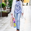 Beautiful woman with shopping bags walking along a commercial st — Stock Photo