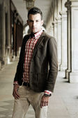 Portrait of a young handsome man, model of fashion, wearing jacket and shirt in urban background — Stock Photo