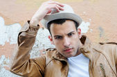 Attractiv young man with a hat in urban background — Stock Photo