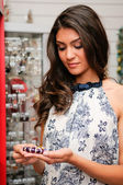 Portrait of attractive young woman buying a bracelet at a jewelry — Stock Photo