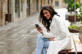 Portrait of beautiful young woman in urban background talking on phone — Stockfoto