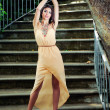 Portrait of a beautiful young woman, model of fashion, in a garden stairs — Stock Photo