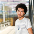 Man with curly hairstyle in urban background — Stock Photo