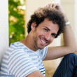 Man with curly hairstyle smiling in urban background — Stockfoto