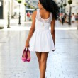 Black woman, afro hairstyle, walking barefoot on a commercial st — Stock Photo #19299371