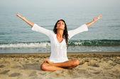 Pretty woman doing yoga on the beach — Stock Photo