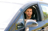 Young man driving a car and looking in the rearview mirror — Stock Photo