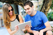 Atractiva pareja con tablet pc en segundo plano urbano — Foto de Stock