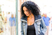 Black woman, afro hairstyle, looking at the shop window — Stock Photo