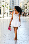 Black woman, afro hairstyle, walking barefoot on a commercial st — Stock Photo