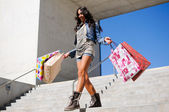 Attractive young girl with shopping bags in the street — Stock Photo