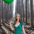Beautiful blonde girl, dressed in green, standing in the forest — Foto de Stock