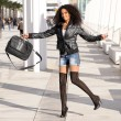 Young pretty black woman jumping in the street with a briefcase — Stock Photo
