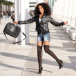 Young pretty black woman jumping in the street with a briefcase - Stock Photo