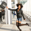 Young pretty black woman jumping in the street with a briefcase — Stock Photo #19316575