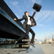 图库照片: Young handsome businessman jumping in the street