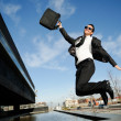 Young handsome businessman jumping in the street — Stockfoto