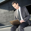 Stock Photo: A businessman sitting on the floor with a laptop computer