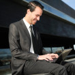 A businessman sitting on the floor with a laptop computer — Stockfoto