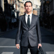 Young handsome businessman standing in the street — Stock Photo