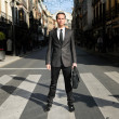 Young handsome businessman standing in a crosswalk — Stock Photo #19318505