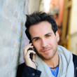 Portrait of handsome man in urban background talking on phone — Stock Photo