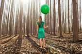 Beautiful blonde girl, dressed in green, standing in the forest — Stock Photo