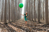 Beautiful blonde girl, dressed in green, laughing in the forest — Stock Photo