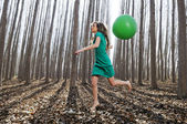 Beautiful blonde girl, dressed in green, jumping into the woods — Stock Photo