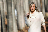 Beautiful blonde girl, dressed with a beige dress, standing in a — Stock Photo