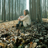 Beautiful blonde sitting on leaves in a forest of poplars — Stock Photo