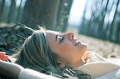 Smiling blonde girl lying on leaves in a forest of poplars — Stock Photo